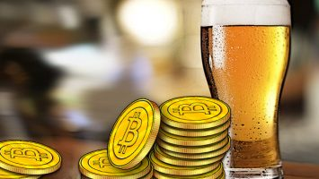 Bitcoin-resting-against-a-pint-of-beer